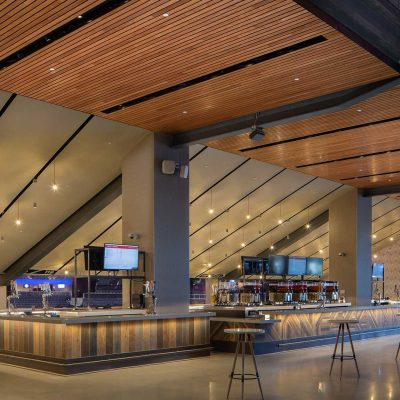 """9Wood's 2300 Continuous Linear in White Oak Veneer with stain at State Farm Arena in Atlanta, Georgia. HOK. Wood adds """"warmth, comfort and a sense of richness to the building,"""" says Architect Emily Louchart of HOK. The photo shows how the subcontractor, Anning-Johnson, successfully coordinated its work, centering the ceiling integrations """"on module"""" in cleanly and symmetrically. Photo: Creative Sources Photography."""