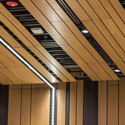 9Wood's 2100 Panelized Linear at the Hyatt Regency Seattle in Seattle, Washington. LMN Architects. The wood panels are assembled with black, shiplap backers each 12 in. o.c. The suspension uses hanger wires to attach 15/16 in. heavy-duty t-bar grid directly to the structure above.