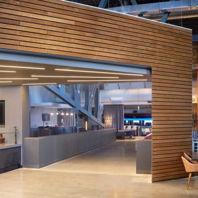 """9Wood's 2300 Continuous Linear in White Oak Veneer with stain at State Farm Arena in Atlanta, Georgia. HOK. The linear wood walls frequently meet at sharp angles. The corner reveals in the back post line up perfectly. This required the subcontractor to define the joinery conditions on site. """"We had to field cut rips in the planks to make everything align,"""" he says."""