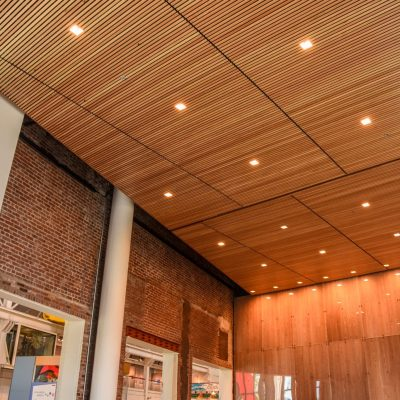 Panel sizes matter when shopping for wood ceilings. By sticking with standard sizes, linear wood ceilings like this one can remain cost effective.