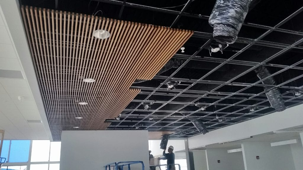 this picture shows a wood ceiling partially installed across an entire suspended tbar grid system.